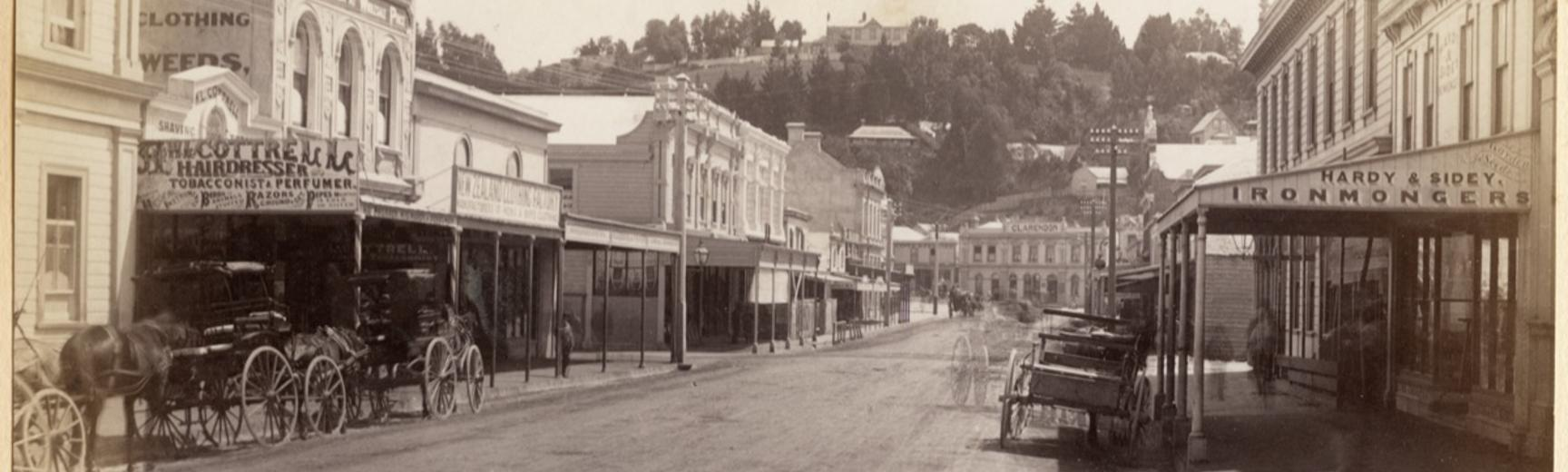 Horse-drawn vehicles stationed outside buildings on Hastings Street in Napier. Photograph by Alfred Burton for the Burton Brothers (Dunedin). Napier, North Island, New Zealand. Circa 1885.