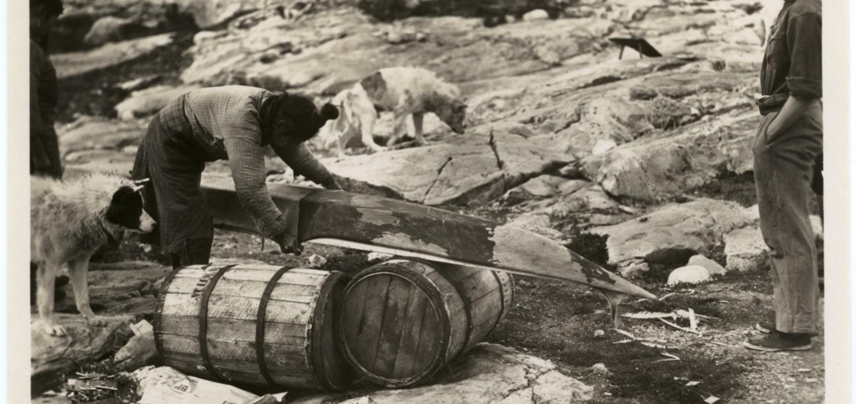 One of the various stages in the construction of a kayak by Inuit, here showing the sewing of a taut sealskin cover. Photographer unknown. Greenland. 1930–1931.