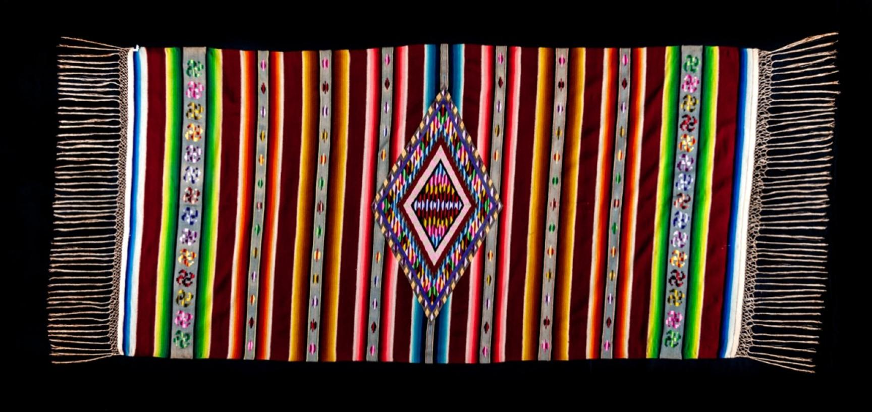 Shawl (saltillo serape), made in the early nineteenth century. Aguascalientes, Mexico. The shawl is tapestry-woven with wool, silk and metallic weft on a linen warp. The gradated bands of colour have been achieved by 'ombre' dyeing, a process whereby the