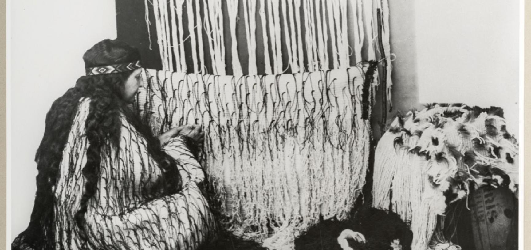 Studio portrait of Makereti, circa 1926. Oddington or Oxford, Oxfordshire, England. Makereti is weaving a dress cloak (korowai) of flax fibre (muka) with black streamers made from the New Zealand kiekie plant and a dyed flax fibre headband (tipare) with a