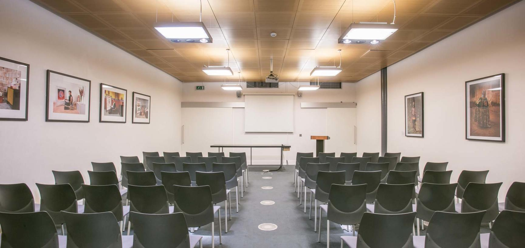 Meeting room with frames on the wall and rows of chairs
