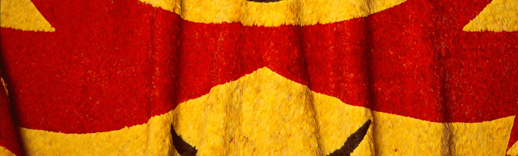 A red, yellow and black feather cloak with geometric designs.  Large yellow triangles have a small black smile shape in  the centre and are outlined in red.