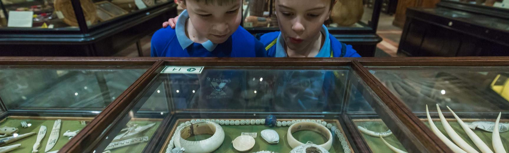 Two boys dressed in school uniform stare in wonder at objects intricately carved from ivory in the case in front of them.