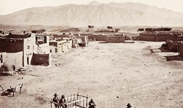 View of the main plaza of Sandia Pueblo, with a wooden cart (known as a carreta) and several people prominent in the foreground, and the Sandia mountains in the distance.