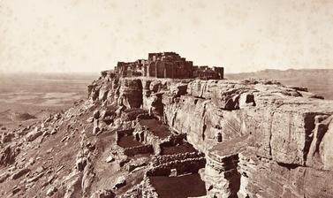 View from Sichomovi of Walpi Pueblo on First Mesa, with stone structures used as goat and sheep pens visible in the foreground.