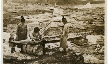 One of the various stages in the construction of a kayak by Inuit, here showing the sewing of a taut sealskin cover. Photograph by Henry Iliffe Cozens. Greenland. 1930–1931.