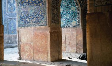 A person prays behind a pillar, beneath the blue tiled walls of the Masjed-e Jāme (Friday Mosque) in Isfahan. Photograph by Sheila Paine. Isfahan, Iran. 1992. (Copyright Pitt Rivers Museum, University of Oxford. Accession Number: 2012.4.2084.1)