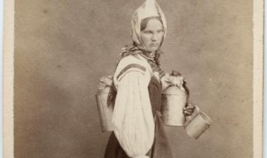 Studio portrait of a Finnish woman, a cream seller, standing, barefoot, carrying several metal jugs. Photograph by the William Carrick studio. St Petersburg, Russia. 1860s. (Copyright Pitt Rivers Museum, University of Oxford. Accession Number: 1941.8.135)