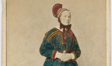 Hand-coloured studio portrait of a Saami woman, identified as a wife (or married woman), standing, wearing a distinctive hat. Photograph by the Marcus Selmer studio. Bergen, Norway. Circa 1873.