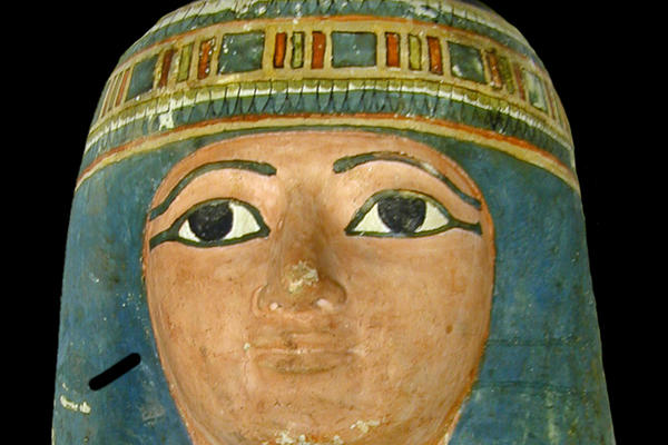 Mummy face with eyes distinctly outlined in black eye liner and a pale indigo wig surrounding the face