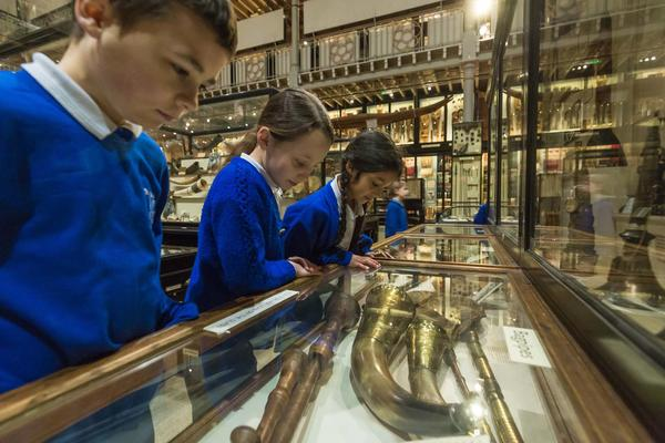 A group of primary school children point at objects in a case in front of them
