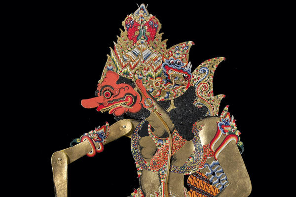 This shadow puppet is of a finely dressed character who has a red face as he is a wicked demon.