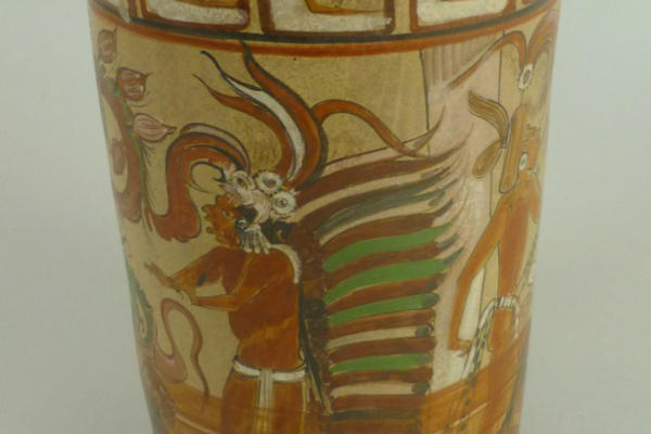 Brown cylindrical vessel painted with a cocoa tree coming out of the body of a male figure.