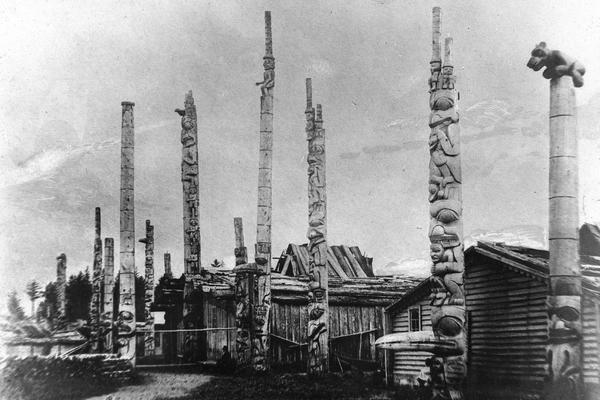 Photograph taken in 1882 showing totem pole in the Haida village of Masset