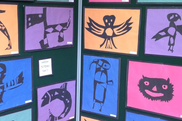 Many different animal silhouettes created using black card stencils on brightly coloured card, such as a fish, a bird and a whale.