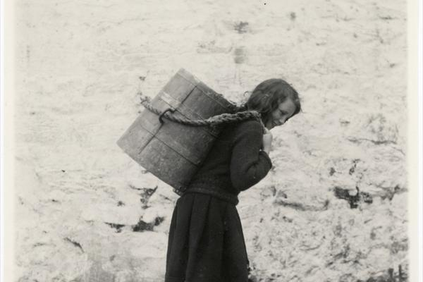 'Young girl carrying a tankard of water from the well. The tankards are made locally of wood bound with iron hoops' (typed caption). Photograph by Thomas H. Mason. Aran Islands, County Galway, Ireland. Undated.