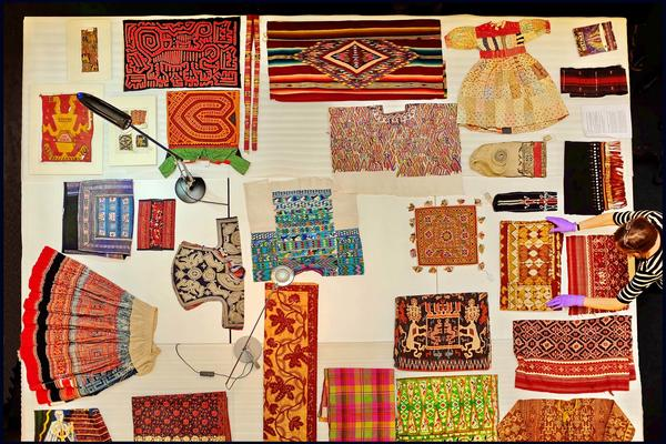 View from above of colourful textiles being laid out on table