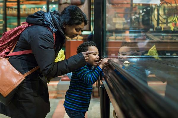 Adult and child looking into display case