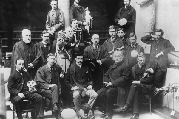 group black and white portrait photo of men posing with a variety of museum objects