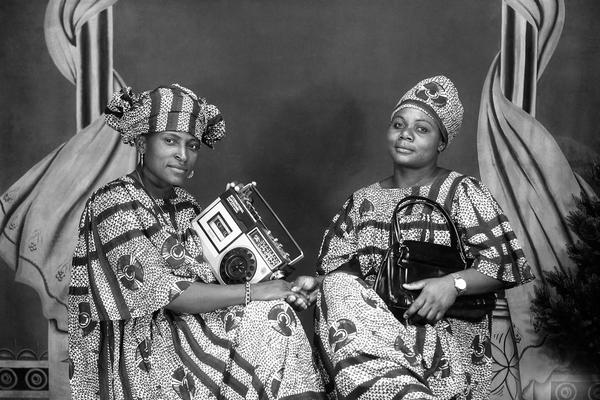 Portrait of two friends holding a cassette player and a handbag, possibly commemorating their purchase of these valued consumer goods. Photograph by Jacques Touselle. Mbouda, Cameroon. About 1975. (Copyright Jacques Touselle)