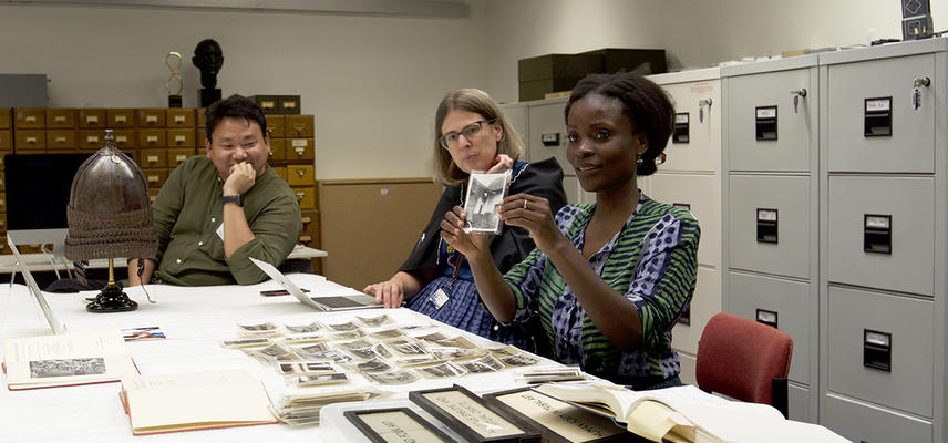 Nana Oforiatta Ayim holding photographs by RS Rattray from 1920s Ghana at Wenner-Gren Workshop