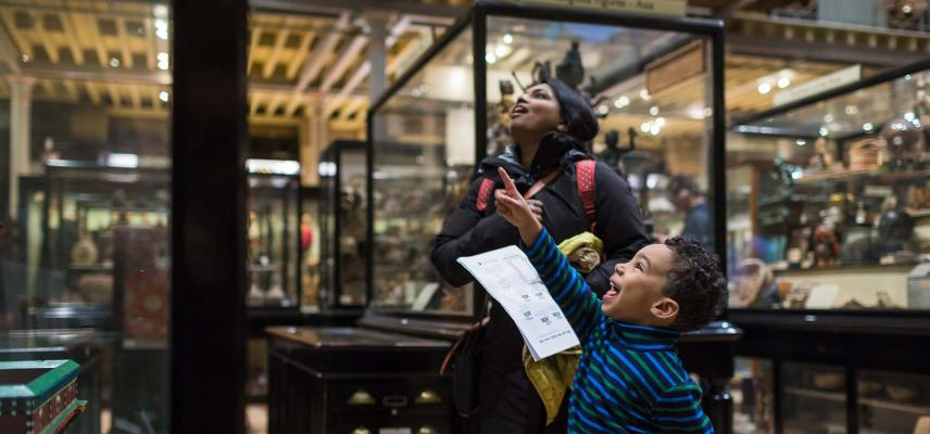 A family looking into a display case at the Pitt Rivers Museum